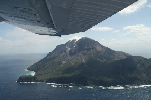 大学の先輩のMさんが飛行機をチャーターして薩摩硫黄島へ日帰りで飛ぶのに同行者を募集していると言う。<br />家人に聞くと、意外にも「行きたい」というので同行することにする。<br />もともと14日に飛ぶ予定だったが、天気が悪いので直前になって15日に変更した。<br />鹿児島には予定の変更が効くように14日入りしていた。<br /><br />霧島に雪もちらついた14日とは打って変わって、15日の鹿児島は雲なしの快晴だった。<br />鹿児島市内のホテルからレンタカーにて集合場所の鹿児島空港へ向かう。<br />鹿児島空港では9:30に待ち合わせ。<br />予定通り、Mさんと落ち合い、新日本航空の方の車で空港南にある本社事務所まで行く。<br />事務所では社長さん直々にご挨拶いただき、手続きなどをする。<br />とはいえ、何かの書類にサインして、お金を払うだけだが。<br />鹿児島~硫黄島のチャーター代は136,500円。高いと言えば高いが、そうそうない機会と考えると出してもいいかなと思える値段。もともとMさんは1人でも行く予定だったので、こちらは2人併せて半額分で許してもらう。。<br />コーヒーをごちそうになり落ち着いてから、いよいよ出発。<br /><br />事務所前すぐに格納庫があり、その前にはすでに飛行機が待機していた。<br />飛行機はセスナ172というものでパイロットを含めて4人乗り。従って満席。<br />パイロットとMさんが全席に乗り、我々2人が後ろに乗る。<br />10時に出発。管制と交信しながら滑走路に向かう。<br />すぐ前に出発する通常の飛行機と比べると心細くなるほどのこぢんまりしている。<br />すんなりと離陸し、枕崎方面に針路をとって進む。枕崎まで30分、そこから海上を30分進むと硫黄島に着く。隣にある竹島・黒島を見て、島の東側からぐるっと島の南側へ回る。島の東には大きな火山があり噴煙をあげているので迫力がある。<br />島の南側から滑走路に着陸する。小さい島で、風の影響とかあるのだろう、なかなか着陸が難しい島だと行っていた。ベテランのパイロットさんで、何の問題もなく無事着陸。<br />飛行場は通常は開いていないが、使用する時は役場の方に事前に連絡して開けておいてもらう。<br /><br />島では、事前にいろいろ問い合わせなどしていたからか、役場の方が待っていてくださった。車で島を案内してくださると言う。<br />まずは島の南端の永良部崎に向かう途中の「岬橋」へ。ここからは集落が一望できる。海は鉄分を含む温泉が湧き出しているため、赤くなっているとのこと。<br />集落を通り過ぎて、硫黄岳の南の麓にある東温泉へ。波打ち際近くに湯船がある。3つの湯船にお湯を順に流し入れることで適温になるようにしている。<br />時間はあまりないが足だけ使ってみる。ここは珍しいミョウバン温泉で澄んだ緑色をしている。口にしてみるとサイダーのような酸っぱい感じの味がする。<br />今度は島の北側の平家城あたりまで行く。硫黄岳を北側から眺める。次は同じく島の北側の坂本温泉へ行く。こちらの方に地元の人がよく来ると行っていたが、たまたまなのかお湯が少なそうであまりちゃんと入れない気がした。<br />そろそろ空港へ戻る。道すがらクジャクが歩き回っていた。昔誰かが持ち込んでそのまま野生化したらしい。<br />結局1時間半ほど滞在して、鹿児島へ戻る。<br /><br />帰りはまっすぐ鹿児島空港に戻る。帰りも1時間かかる。14時頃、無事に鹿児島空港到着して終了。<br /><br /><br />