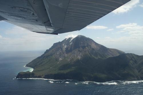 大学の先輩のMさんが飛行機をチャーターして薩摩硫黄島へ日帰りで飛ぶのに同行者を募集していると言う。<br />家人に聞くと、意外にも「行きたい」というので同行することにする。<br />もともと14日に飛ぶ予定だったが、天気が悪いので直前になって15日に変更した。<br />鹿児島には予定の変更が効くように14日入りしていた。<br /><br />霧島に雪もちらついた14日とは打って変わって、15日の鹿児島は雲なしの快晴だった。<br />鹿児島市内のホテルからレンタカーにて集合場所の鹿児島空港へ向かう。<br />鹿児島空港では9:30に待ち合わせ。<br />予定通り、Mさんと落ち合い、新日本航空の方の車で空港南にある本社事務所まで行く。<br />事務所では社長さん直々にご挨拶いただき、手続きなどをする。<br />とはいえ、何かの書類にサインして、お金を払うだけだが。<br />鹿児島?硫黄島のチャーター代は136,500円。高いと言えば高いが、そうそうない機会と考えると出してもいいかなと思える値段。もともとMさんは1人でも行く予定だったので、こちらは2人併せて半額分で許してもらう。。<br />コーヒーをごちそうになり落ち着いてから、いよいよ出発。<br /><br />事務所前すぐに格納庫があり、その前にはすでに飛行機が待機していた。<br />飛行機はセスナ172というものでパイロットを含めて4人乗り。従って満席。<br />パイロットとMさんが前席に乗り、我々2人が後ろに乗る。<br />10時に出発。管制と交信しながら滑走路に向かう。<br />すぐ前に出発する通常の飛行機と比べると心細くなるほどのこぢんまりしている。<br />すんなりと離陸し、枕崎方面に針路をとって進む。枕崎まで30分、そこから海上を30分進むと硫黄島に着く。隣にある竹島・黒島を見て、島の東側からぐるっと島の南側へ回る。島の東には大きな火山があり噴煙をあげているので迫力がある。<br />島の南側から滑走路に着陸する。小さい島で、風の影響とかあるのだろう、なかなか着陸が難しい島だと行っていた。ベテランのパイロットさんで、何の問題もなく無事着陸。<br />飛行場は通常は開いていないが、使用する時は役場の方に事前に連絡して開けておいてもらう。<br /><br />島では、事前にいろいろ問い合わせなどしていたからか、役場の方が待っていてくださった。車で島を案内してくださると言う。<br />まずは島の南端の永良部崎に向かう途中の「岬橋」へ。ここからは集落が一望できる。海は鉄分を含む温泉が湧き出しているため、赤くなっているとのこと。<br />集落を通り過ぎて、硫黄岳の南の麓にある東温泉へ。波打ち際近くに湯船がある。3つの湯船にお湯を順に流し入れることで適温になるようにしている。<br />時間はあまりないが足だけ使ってみる。ここは珍しいミョウバン温泉で澄んだ緑色をしている。口にしてみるとサイダーのような酸っぱい感じの味がする。<br />今度は島の北側の平家城あたりまで行く。硫黄岳を北側から眺める。次は同じく島の北側の坂本温泉へ行く。こちらの方に地元の人がよく来ると行っていたが、たまたまなのかお湯が少なそうであまりちゃんと入れない気がした。<br />そろそろ空港へ戻る。道すがらクジャクが歩き回っていた。昔誰かが持ち込んでそのまま野生化したらしい。<br />結局1時間半ほど滞在して、鹿児島へ戻る。<br /><br />帰りはまっすぐ鹿児島空港に戻る。帰りも1時間かかる。14時頃、無事に鹿児島空港到着して終了。<br /><br /><br />