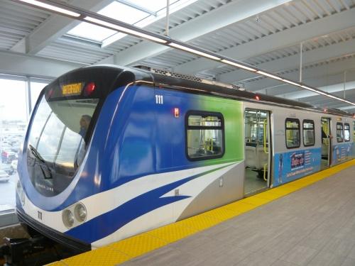 カナダライン。<br />http://www.translink.ca/en/Rider-Info/Canada-Line/Map-and-Travel-Times.aspx<br /><br />バンクーバー国際空港からバンクーバー市内へのアクセス用に<br />2009年夏に開通した新交通システム。<br />あまり鉄道のことは詳しくはありませんが、無人で運行して<br />おり、地下鉄のように車輪のところから電気を吸収して走って<br />います。<br /><br />路線はダウンタウンのウォーターフロント駅から郊外のリッチ<br />モンド・ブリッグハウス駅を25分で結んでおり、途中の<br />ブリッジポート駅からバンクーバー国際空港駅行きの支線に<br />分かれています。<br />空港駅からウォーターフロント駅までは26分です。<br /><br />バンクーバー国際空港駅からはウォーターフロント駅行き<br />しかありませんので乗り間違えることはありませんが、<br />逆のウォーターフロント駅からは、空港行きとリッチモンド・<br />ブリッグハウス駅行きが交互に走っていますので、<br />乗り間違えには注意が必要です。<br />リッチモンド・ブリッグハウス駅行きに乗ってもブリッジ<br />ポート駅で乗り換えれば大丈夫ですが結局は後続の列車に<br />なってしまいます。<br /><br />バンクーバー国際空港駅の始発は5時10分、終電は0時57分、<br />逆のウォーターフロント駅から空港行きの始発は4時50分、<br />終電は1時05分となっています。<br /><br />運行間隔は6分〜10分です。<br />バンクーバー国際空港駅を出た列車はしばらく高架を走り<br />ますが、マリンドライブ駅を過ぎたところで終点のウォーター<br />フロント駅まで地下を走ります。<br /><br />チケットは自動券売機で購入します。<br />自動券売機はタッチパネルになっています。<br />まずは、路線図を見て、行きたい駅がどのゾーンかを確認<br />します。<br />1ゾーン、2ゾーン、3ゾーン制になっており、行くべき駅の<br />ゾーンボタンを押し、次にお金を投入します。<br />コインは5・10・25セント、1・2ドルが使えます。<br />紙幣は5・10・20ドルが使えます。<br />これ以外は使えませんので、事前に用意しておきましょう。<br /><br />チケットを購入してホームに行きますが、その途中、改札は<br />ありません。<br />そして列車はワンマンで運行していますのでキセルをしようと<br />思えばできますが、それは犯罪ですので止めましょう。<br /><br />運賃は、平日・週末・時間帯によって異なります。<br /><br />ちなみに空港からダウンタウンまでの運賃は大人8.75カナダ<br />ドル。ダウンタウンから空港までは3.75カナダドル。<br /><br />なぜ???