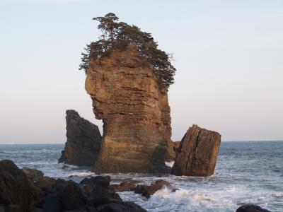 三王岩は高さ50メートルを越す男岩と浸食の進んだ女岩、太鼓の形をした太鼓岩の3つの岩からなる。男岩には直径2メートルほどの海蝕洞があり、この穴をくぐると幸せになれるという言い伝えがある。<br /> 三陸鉄道北リアス線田老(たろう)駅に降り立ち、駅前のタクシー営業所で風光明媚な所がないか聞くと三王岩があるという。タクシーで浜に向かうと水門があり、町を高い防潮堤が取り囲んでいる。浜に出る道路にある水門は、津波の時には閉じて町を守るのだ。宮古市田老町(たろうちょう)はリアス式海岸の湾の奥に位置し、幾度も津波の被害を受けているため、高さ10m、総延長2.5kmにも及ぶ防潮堤を建設しているのだ。三陸海岸は深いリアス式海岸になっているために、地球の裏側で地震が起きても津波が襲ってくることがあった。Tsunamiが世界の共通語になったのはここ三陸海岸の津波の被害があったからであろう。この防潮堤を見ると、リアス式海岸が風光明媚な海岸線を作り出しているなどと流暢なことばかりは言ってはいられない。まずはこの地に暮す人々の生命・財産を守らなければならないことを知った。<br />(表紙写真は田老町三王岩)