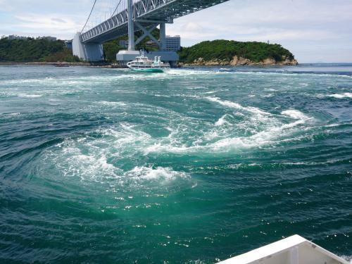 """渦潮を見に鳴門へ。<br />以前大鳴門橋の""""渦の道""""から渦を巻いてない海を見たことがありましたが、今回は観潮船に乗って海から見ることにしました。<br /><br />潮見表で満潮干潮時刻を調べてみたら本日は12時30分干潮。<br />満潮干潮の前後一時間半までが渦潮の見頃とのこと。<br /><br />船会社がいくつかあるようですが、今回は鳴門観光汽船の""""アクアエディ""""という小型水中観潮船をchoice。<br />同じ船着き場から""""わんだーなると""""という大型観潮船も出ていました。<br /><br />天気は晴れ。大潮。海もまずまず穏やかとチケット売り場のおじさんに教えてもらい、いざ渦潮へ。<br /><br />初めて見た渦潮は豪快というよりは神秘。<br />タイミングに依るところが大きいですが、一見の価値ありです。"""