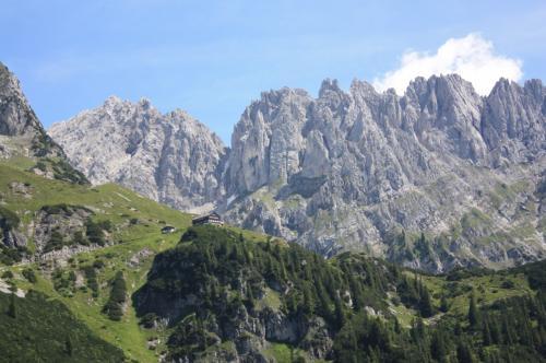 オーストリアのチロル州にある皇帝山脈(Kaisergebirge)。<br />長年憧れていた皇帝山脈へ、ハイキングする日がついにやってきました。<br />皇帝山脈は、南側にあるWilder Kaiserと、北側にあるZahmer Kaiserという<br />2つの山脈から成り立っています。<br />今回私がハイキングしたのは、南側のWilder Kaiserの方です。<br /><br />私は登山初級レベルです。あらかじめドイツの版元が出している<br />Wilder Kaiserの山歩きのガイドブックを取り寄せて、<br />自分でも登れそうなコースをいくつか調べておきました。<br />中でも一番行きたかったコースが今回歩いたコースです。<br /><br />Wilder Kaiserは切り立った岩山ですから、登山上級者の方なら<br />山頂まで行けるのですが、私は初級者なので<br />中腹のGruttenhuetteまで行くコースを歩きました。<br />実際歩いてみると、とても眺めが良いコースで、初級者でも歩け、<br />Gruttenhuetteに着くと、壮大なWilder Kaiserを間近に望むことができました。<br />この表紙の写真は、ハイキングコースの途中から撮ったWilder Kaiserです。<br />イタリアのドロミテのように見えるかもしれませんが、<br />ここはオーストリアのチロルです。<br />ドイツと国境を接するクーフシュタインから奥に入った、エルマウ村のあたりです。<br /><br />写真が多いので、旅行記を前編と後編に分けました。<br />この旅行記は前編で、ホテル出発→Wochenbrunner Almから<br />目的地のGruttenhuetteまでの記録です。<br />