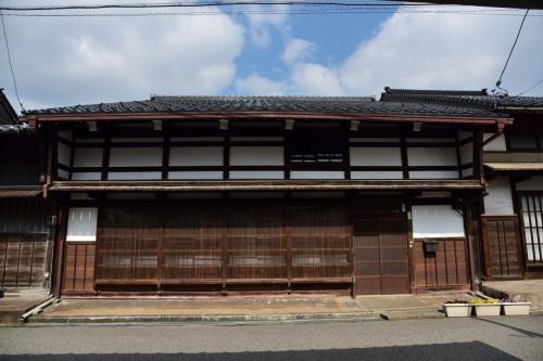 春の青春18きっぷを使って富山を訪れました。<br /><br />旅の行程<br />4月2日 越中八尾<br />4月3日 越中岩瀬、射水市二口、越中福岡<br />4月4日 高岡市吉久、南砺市福光<br /><br />富山県高岡市吉久は、高岡市と射水市を結ぶ路面電車、万葉線吉久駅の東側に広がる町で、小矢部川と庄川に挟まれた細長い中洲にある近代的な工場群を縫うように、今も江戸時代の湾曲した道筋がそのまま残る放生津街道沿いには、まるで周囲の喧騒や時間の流れから取り残されたかのように、幕末から昭和初期に建てられた重厚な町家が連なる、風情ある町並みが広がっています。<br /><br />江戸時代初期、小矢部川の水運により集められる領内の年貢米を保管するため、加賀藩の御蔵が造られたのをきっかけに発展した吉久は、米の流通に関する豊富な経験や知識の蓄積から、御蔵が廃止された後も、豊かな経済力を背景に米商人の町として栄えました。<br /><br />この地域の町家の伝統的な様式である、切妻屋根の平入り、出桁造りの中2階建てに、頑丈な袖壁や千本格子をしつらえ、1階の下屋より2階の大屋根の方が長く張り出した町家が連なる町並みは、同じ高岡市内の山町筋や金屋町にも見劣りしない、見事な町並みを展開しています。<br /><br />しかし、山町筋や金屋町の賑わいのある町並みに対して、観光地化されていない吉久はひっそりとした生活の場といった感が強く、建物や町並みそのものは山町筋や金屋町に見劣りしないとは言うものの、町の雰囲気は随分異なっています。