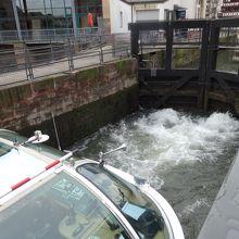 船前方の閘門の隙間から上流の水が流入する