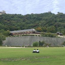 松山城を望む芝生の広場に女子高生が遊ぶ