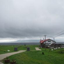 広大な草原の丘に海の先にそびえる利尻富士