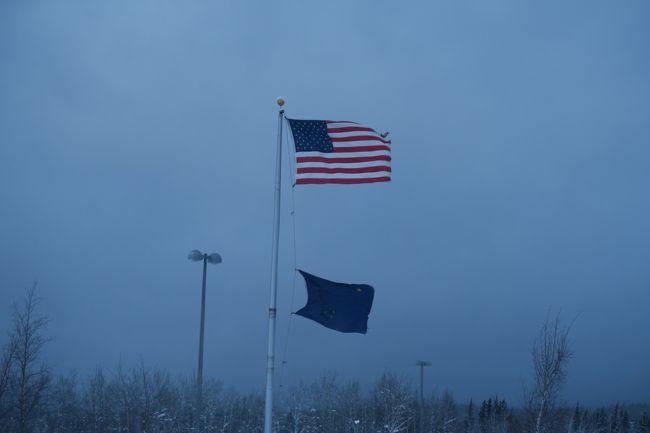 この年末年始は世間と休みが違うらしく、良いと思ったツアーは日程が合わず、ウダウダ決めあぐねていたら、チャーター便で行くアラスカのツアーを発見。<br />クラブツーリズム貸切のチャーター便で、前回より1日少ないが、チェナ温泉3泊に申し込む。<br /><br />2年ぶりのオーロラ鑑賞、6年ぶりのアラスカ。<br />しかし、前回はすばらしいオーロラが見れたが、出発前の天気予報では3日とも曇りだったので、不安いっぱい。<br /><br />3時半ごろ出発したが、首都高までが思いのほか混んでいて、駐車場に付いたのが5時20分ごろ。<br />空港に付いたのが、集合時間の5時半。<br />急いでカウンターに向かうと、まだたくさんの人が並んでいて一安心。<br /><br />今回はクラブルーリズムで貸切なので、全体で約230人の大所帯。<br />それが9組ぐらいに分かれて、我が家はその中で恐らく最小の10人のグループに参加。<br /><br />数年前に両替したドルが、たくさん余っていたので、今回は両替なし。<br />しかし、ハンカチを忘れたので探すが、唯一売っていたお店はレジが長蛇の列だったので、諦めて出国。<br />手荷物検査もパスポートチェックも、少し並んだだけ。<br /><br />免税店でお土産とハンカチを買っていたら、集合時間まで30分を切っていたので、急いで搭乗ゲートに向かうと、当然、たくさんの人たちでごった返していた。<br /><br />添乗員ではないお世話係りの人から説明を聞いたあと、すぐに搭乗開始。<br />運よく、ゲートの横にいたので、すぐに搭乗できた。<br />定刻過ぎにブリッジを離れたものの、15分以上かけて滑走路に移動。<br /><br />ただ今回のチャーター便は、あのウズベキスタン航空。<br />B767なのでパーソナルモニターは有ったものの、映画は数も少いうえに、ほとんどがウズベキスタンやロシア製。<br />仕方なく、ゲームで時間を潰す。<br /><br />ほぼ定刻どおり、フェアバンクスに到着。<br />グループごとに飛行機を降りるので、われわれは4番目。<br />当然、カードをもらって、控え室で入国審査待ち。<br /><br />1時間以上待って、やっと入国。<br />外は、どんより曇り空。<br />やはり予報通りか。<br /><br />当初、空港で防寒着を借りることになっていたが、やはりそんなことはなく前回も行ったウェストマークホテルに移動。<br />防寒着をも借りてチェナに移動するはずが、前日の大雪のため、除雪が終わっているかわからないということで、ホテルで待機。<br /><br />昼食もないので、仕方なく、日本から持って行ったお菓子を食べて小腹を満たす。<br />結局、我々の乗るはずのバスは来ず、別の添乗員付きのコースのバスに乗せてもらってチェナに行くことに。<br />それでも2時間ぐらい時間があったので、お世話係の人が、ホテルの人に近くにCO-OPがあると聞き、みんなで行くことに。<br />しかし、行けどもそれらしきお店がなく、お世話係の人が聞いたりして探してくれたが、どうやらガセネタだったらしく、諦めてホテルに戻る。<br />個人的には、良い時間つぶしになった上に散歩できて良かった。<br /><br />4時過ぎバスが到着し、ほぼ満員のバスでチェナに向かう。<br />このコースは途中スーパーに寄ることになっていたので、大急ぎで買い物をして、出発することに。<br />結果的にチェナに着くのは遅くなったが、途中でスーパーに寄れたので、プラマイゼロか?<br /><br />6時半ごろチェナに無事到着し、チェックインに少し時間がかかったが、部屋に入ってすぐに夕食へ。<br />2組待っていたが5分ほどでテーブルに案内してもらえて、サーモンは肉厚で、とても美味しかった。<br />但し、混雑していたのか食べ終わるまで1時間ほどかかった。<br /><br />食べ終わっても雪は降りやまず、諦めて寝ることに。<br />途中、2回起きて外に出てみたが、全く雪はやむことはなかった。