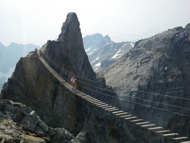 それはインスタグラムの一枚の写真から始まった。<br />絶壁と絶壁の間に渡された長い吊り橋。そこを渡る人の姿。下を見れば目もくらむほど底無しの峡谷。<br />こんなスゴイところがあるんだ~。きっとプロの登山家が行くんだろうな~。<br />初めはそう思っていたが、調べてみると、ヴィアフェラータといってロープで固定して安全に渡れるようになっており、<br />クライミングなどの特別な技術がなくても行けるらしい・・・。<br /><br />去年コルチナ・ダンペッツォでヴィアフェラータを見たこともあり、<br />体力のある今のうちにやってやろうじゃないかっと、決めました!!<br /><br />しっかし、ヴィアフェラータの紹介ビデオなどを見る度に<br />「本当に行けるんだろうか?」<br />「途中で怖くて動けなくなったらどうしよう?」<br />「体力が続くんだろうか?」<br />「ホントに安全?ホントにホント?」<br /><br />など不安が次々沸き起こる。<br /><br />だがしかし~ここまで来たら行くっきゃない~~。<br /><br />ということでヘリコプターで山荘に飛び、そこで3泊過ごして、天上のハイキングとヴィアフェラータをしてきました。<br /><br />これはその1日目の旅行記です。<br /><br />表紙写真はきっかけとなった天空の吊り橋。<br />渡っているのは私ではありません。<br />さて、私は本当にここへ行けたのでしょうか?<br />あなたなら渡りますか?